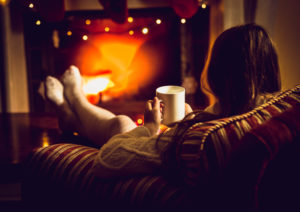 Photo of woman warming up with hot tea at fireplace at winter