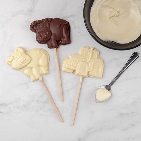 Milk and white chocolate farmyard animal shaped lollies on worktop