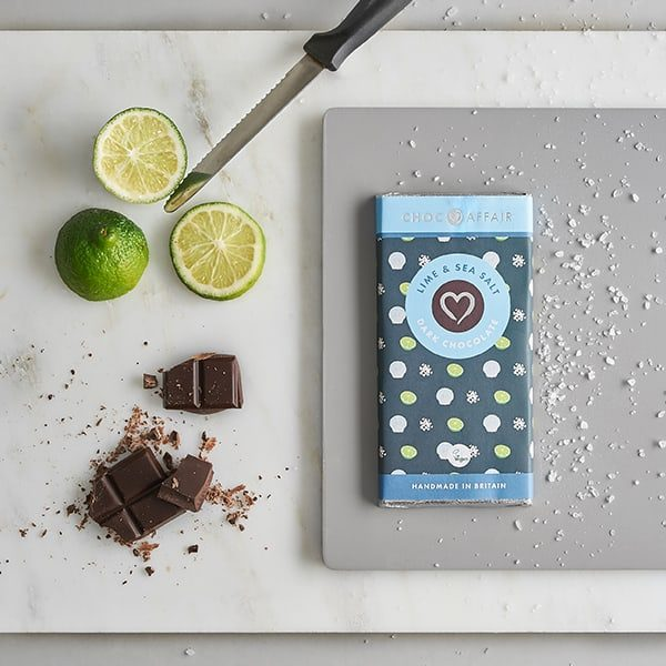 Lime & sea salt dark chocolate bar on chopping board with lime and salt
