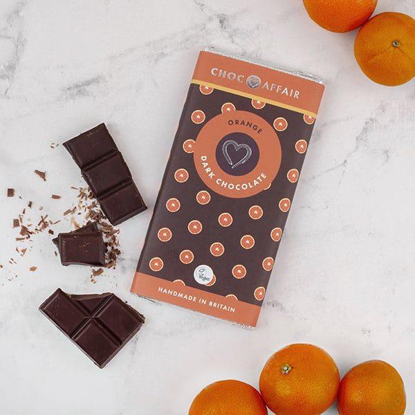Orange dark chocolate bar on worktop with oranges