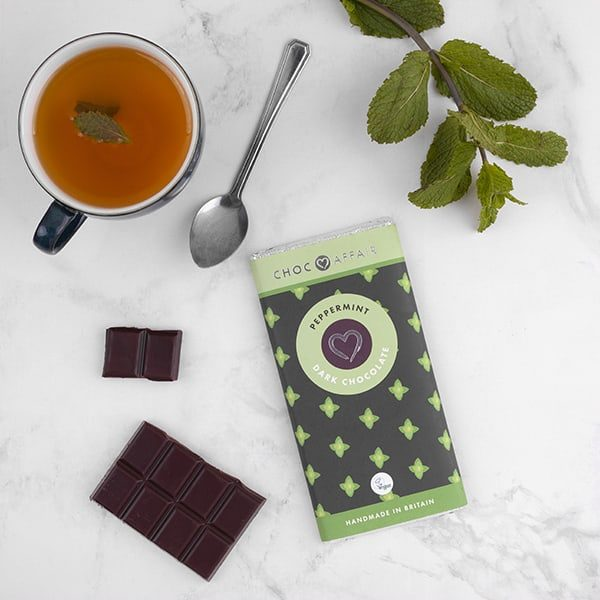 peppermint dark chocolate bar on worktop with mint tea and mint leaves