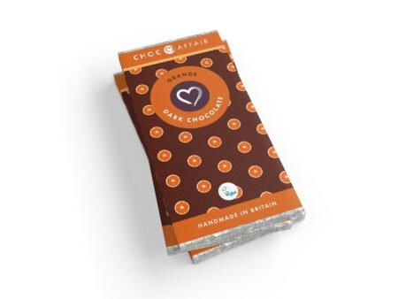 A stack of orange dark vegan chocolate bars against a white background.