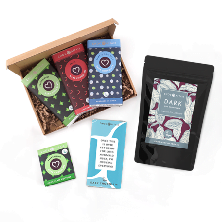 A selection of vegan registered dark chocolate bars and dark hot chocolate in a box on a white background.