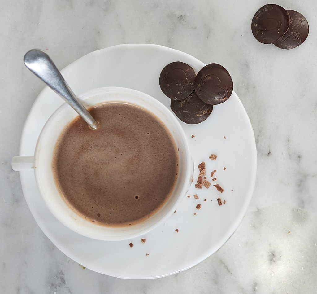 Cup of hot chocolate and chocolate buttons on the side.